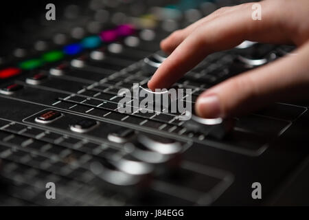 Hand of female audio engineer using sound mixer in recording studio - Stock Photo