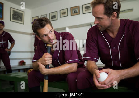 Baseball players sitting together on bench in locker room - Stock Photo