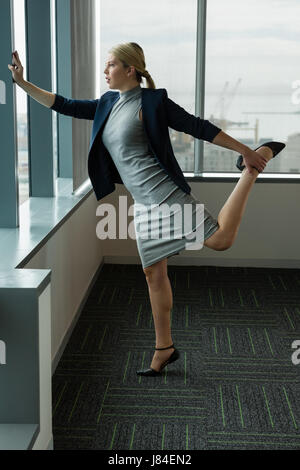 Executive performing stretching exercise near window in office - Stock Photo