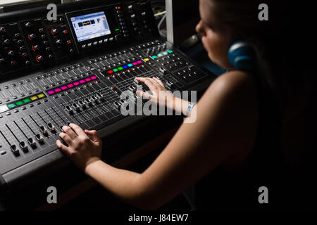 Female audio engineer using sound mixer in recording studio - Stock Photo