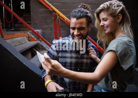 Couple taking selfie on mobile phone outside the bar - Stock Photo