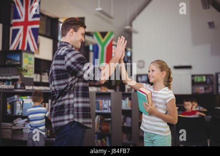 Happy teacher and schoolgirl giving high five in library at school - Stock Photo