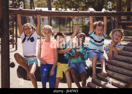schoolkids having fun on tyre swing at school playground - Stock Photo