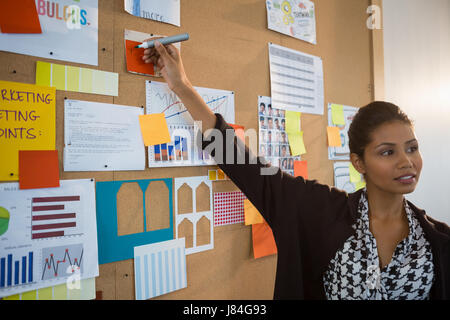 Female executive pointing at sticky note on bulletin board at office - Stock Photo
