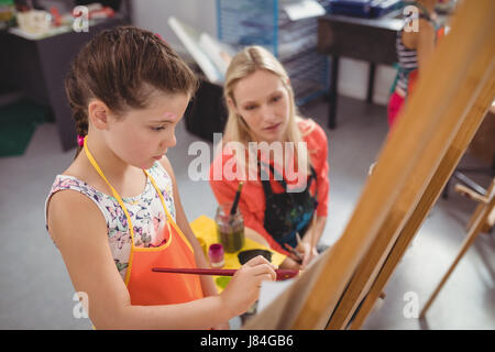 Teacher assisting girl in drawing class at school - Stock Photo