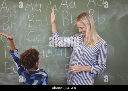Happy teacher and schoolboy giving high five in classroom at school - Stock Photo