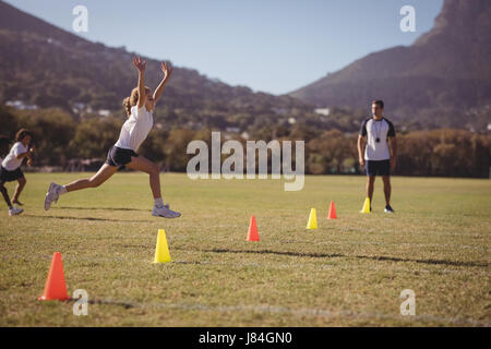 Schoolgirl running towards fining line during competition in park - Stock Photo