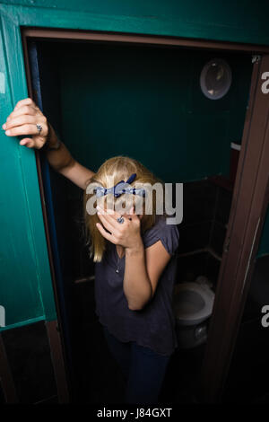 Unconscious drunk woman standing in the washroom - Stock Photo