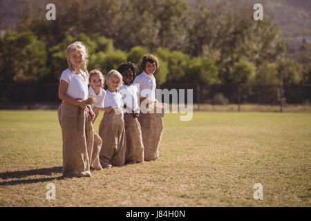 Portrait of happy schoolgirls standing in sack during race on a sunny day - Stock Photo
