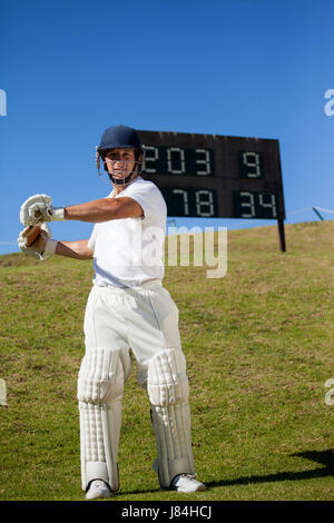 Confident cricket player swinging bat while standing against scoreboard at field - Stock Photo