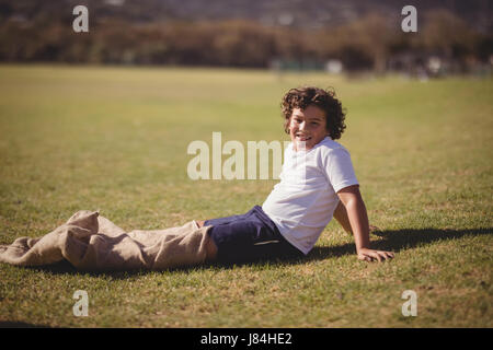 Portrait of happy schoolgirl preparing for sack race in park on a sunny day - Stock Photo