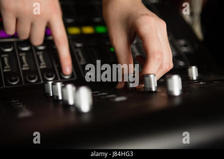 Hands of female audio engineer using sound mixer in recording studio - Stock Photo
