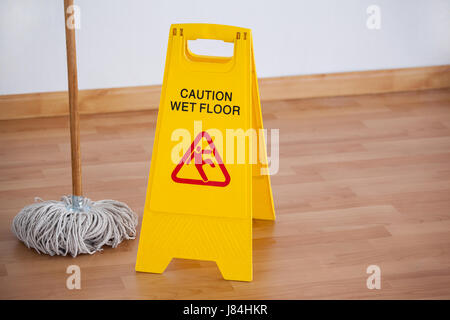 Mop with wet floor caution sign on wooden floor - Stock Photo