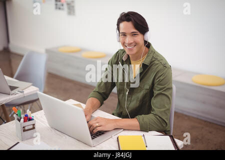 Portrait of smiling businessman working over laptop at desk while wearing headphones in creative office - Stock Photo