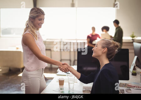 Smiling female business people shaking hands at creative office desk - Stock Photo