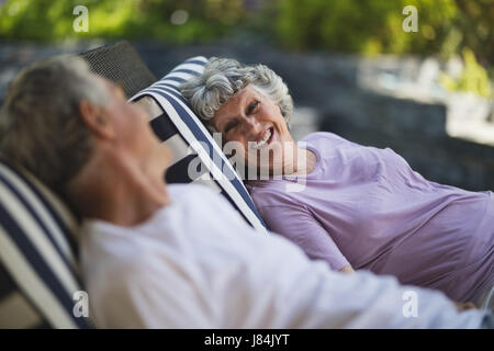 Smiling senior woman looking at man resting together on lounge chairs - Stock Photo