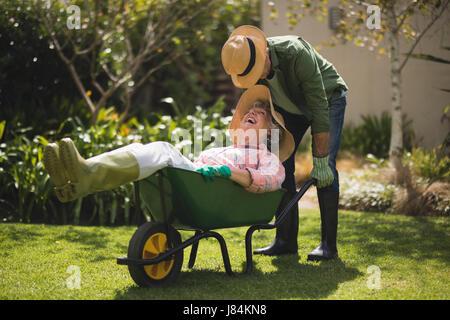 Senior man carrying smiling woman in wheel borrow at yard - Stock Photo