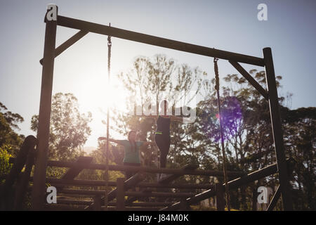 Women walking on outdoor equipment during obstacle course in boot camp - Stock Photo