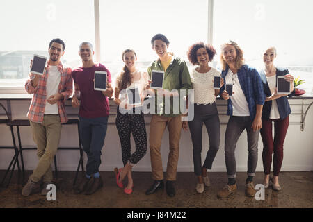 Portrait of smiling business team showing technologies while standing against window at creative office - Stock Photo