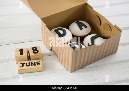 High angle view of cupcakes with text in box by calender on white table - Stock Photo