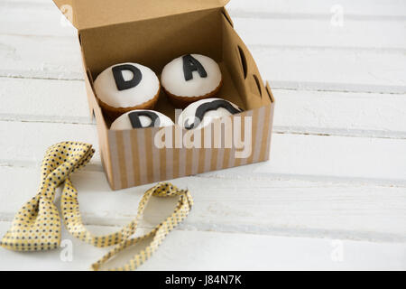 High angle view of cupcakes with text in box by bow tie on white table - Stock Photo