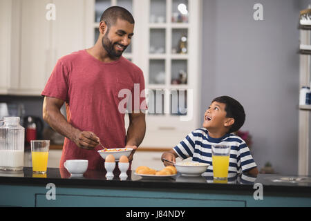 Happy young father with his son having breakfast in kitchen at home - Stock Photo