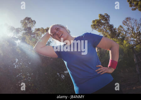 Tired woman standing with hand on hip in the boot camp on a sunny day - Stock Photo