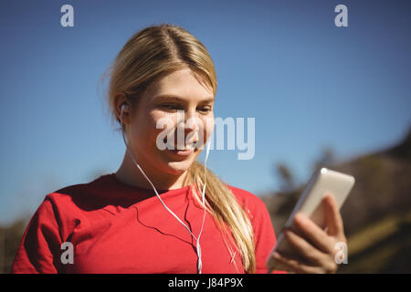 Fit woman listening music on mobile phone during obstacle course in boot camp - Stock Photo