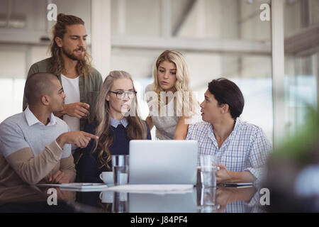 Group of serious business people working on laptop in office - Stock Photo