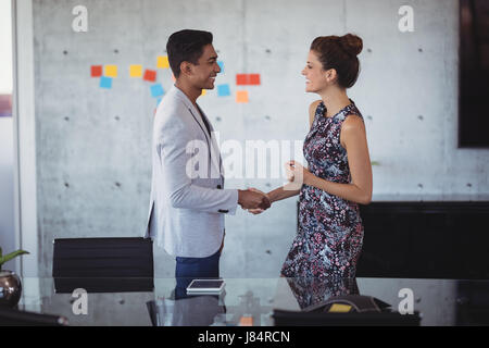 Side view of young business people shaking hands at creative office - Stock Photo
