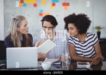 Confident business people using digital tablet while making strategies in creative office Stock Photo
