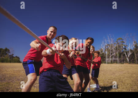 Trainer assisting kids in tug of war during obstacle course training in the boot camp - Stock Photo