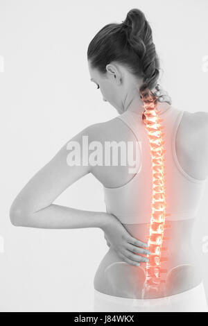Rear view of female suffering from pain against white background