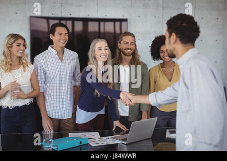 Smiling young business people shaking hands at desk in creative office - Stock Photo