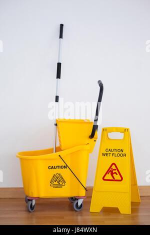 Mop Bucket And Caution Sign On Wet Floor Stock Photo