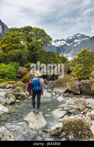 Female hiker on a rock in the river, Fiordland National Park, Southland, New Zealand
