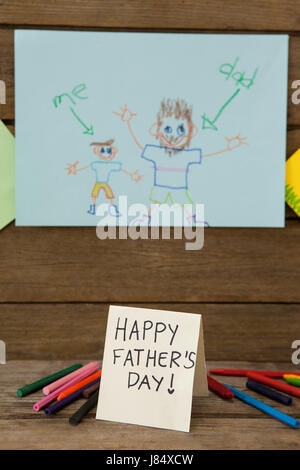 Paintings on drawing paper with happy fathers day message on wooden plank - Stock Photo