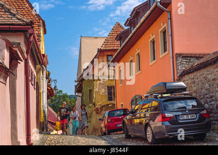 Sighisoara, Romania - July 26, 2014: Tourists stroll the narrow cobblestone streets in the historic center of Sighisoara. - Stock Photo