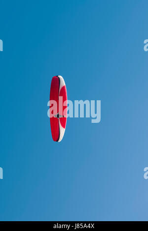 Colorful hang glider in sky over blue. - Stock Photo