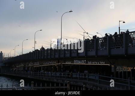 ISTANBUL, TURKEY - MAY 19, 2017: Fishermen fishing on Galata Bridge. Galata Bridge is the most popular destinations - Stock Photo