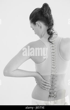 Rear view of female suffering from neck pain against white background
