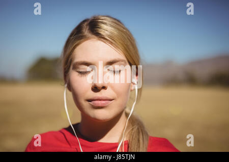 Fit woman listening music on headphones during obstacle course in boot camp - Stock Photo