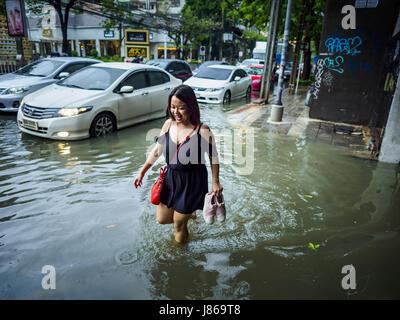 Bangkok, Bangkok, Thailand. 27th May, 2017. A woman walks on a sidewalk flooded by monsoonal rains along Ekkamai - Stock Photo