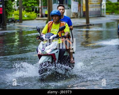 Bangkok, Bangkok, Thailand. 27th May, 2017. A motorcyle taxi with a passenger on Ekkamai Road, flooded by monsoonal - Stock Photo