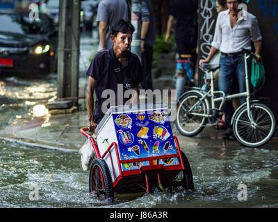 Thailand. 27th May, 2017. An ice cream vendor pushes his cart along a sidewalk flooded by monsoonal rains on Ekkamai - Stock Photo