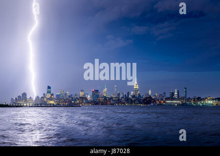 Lightning striking Midtown New York City skyscrapers at night. Stormy skies over Manhattan from the Hudson River - Stock Photo