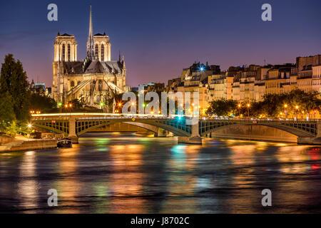 Notre Dame de Paris Cathedral, Seine River and the Sully Bridge at twilight. Summer evening on Ile Saint Louis, 4th Arrondissement in Paris. France