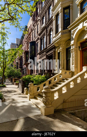 Row of brownstones with doorsteps and ornament in morning light. Upper West Side Street, Manhattan, New York City - Stock Photo