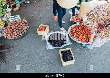 NHA TRANG, VIETNAM - JANUARY 20: Woman is selling strawberry and mulberry at the wet market on January 20, 2016 - Stock Photo