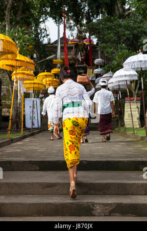UBUD, INDONESIA - MARCH 2: Woman walks up the stairs during the celebration before Nyepi (Balinese Day of Silence) - Stock Photo